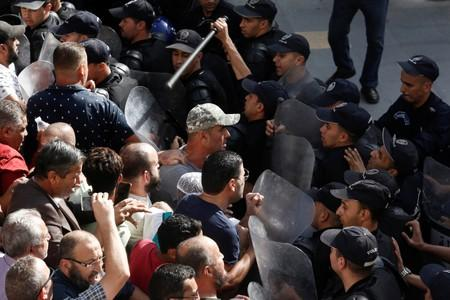 Police officers try to disperse demonstrators during a protest against a proposed new hydrocarbons law in Algiers