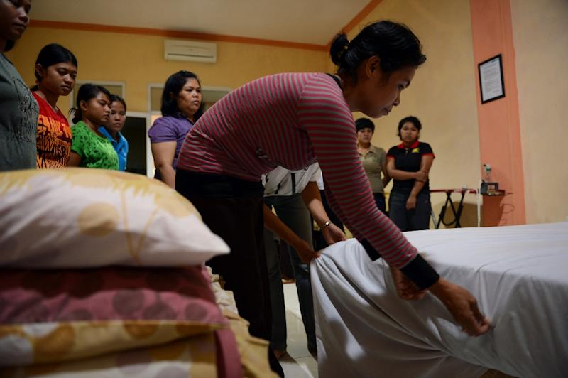 An Indonesian maid learns to fix a bed in Jakarta, during a class for a group of maids undergoing training at a private recruitment agency, in January 2014 (AFP Photo/Romeo Gacad)