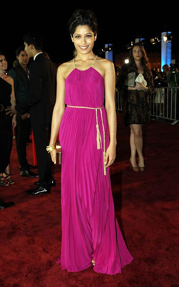 """""""Slumdog Millionaire"""" alum Freida Pinto turned heads in Salvatore Ferragamo at the Doha Film Fest in Qatar. The beauty's magenta, custom-made gown included a gold rope belt, which matched her Amrapali bracelets and clutch. (10/25/11)"""