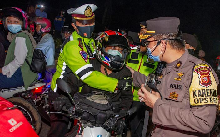 """Police officers halt a motorist at a checkpoint as Indonesia imposes restrictions on mass travel ahead of the Eid al-Fitr celebrations known as """"mudik"""" in an effort to prevent a large-scale transmission - Antara Foto/Reuters"""