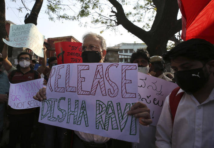 """FILE - In this Feb. 15, 2021, file photo, prominent Indian historian Ramachandra Guha, center, holds a placard demanding the release of Indian climate activist Disha Ravi during a protest in Bengaluru, India. Ravi, a 22-year-old climate activist in India, was arrested and charged with sedition last month for sharing an online handbook meant to help raise support for farmer protests that have convulsed India. The incident has called into question the state of India's democracy, with observers decrying it as the latest attempt by Prime Minister Narendra Modi's Hindu nationalist government to mute dissent. Guha said previous governments have also tried to control independent institutions but """"a recovery, even a partial one,"""" always followed. """"I fear that this time our democratic traditions may not be able to recover from this assault,"""" he said. (AP Photo/Aijaz Rahi, File)"""
