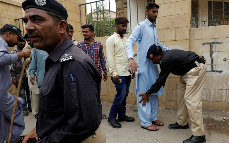 A police officer checks mock voters while other looks on, as they perform a rehearsal for security measures, outside a polling booth, ahead of general elections in Karachi, Pakistan - REUTERS