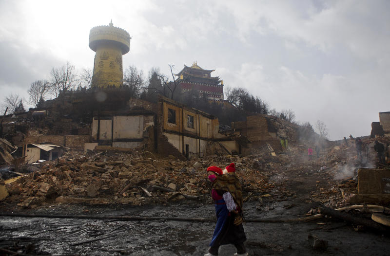 In this Sunday, Jan. 12, 2014 photo, a woman carrying a toddler walks past debris of burnt houses in the ancient town of Dukezong after a fire broke out on last Saturday, in Shangri-la county in southwest China's Yunnan province. A fire prevention system costing more than $1 million wasn't functioning and failed to prevent a blaze that razed the ancient tourist town, the fire service said Monday. (AP Photo) CHINA OUT