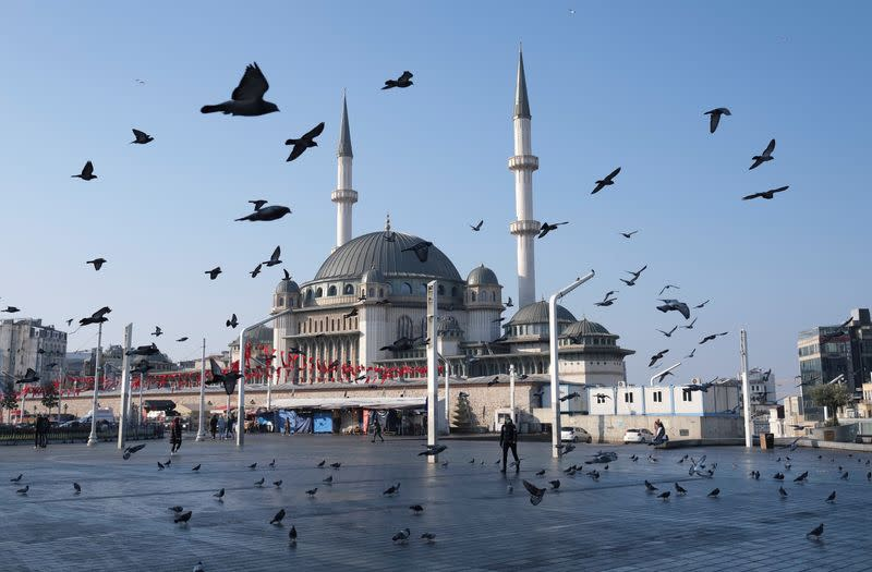 Pigeons fly over the Taksim Square during a nation-wide weekend curfew in Istanbul