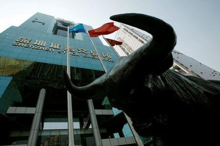 FILE PHOTO: A statue of a bull is displayed outside the Shenzhen Stock Exchange in the southern Chinese city of Shenzhen
