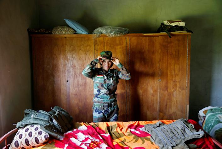 Asema Dahir, 21, adjusts her cap in a bedroom near the front line.