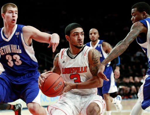 Louisville's Peyton Siva (3) passes away from Seton Hall's Patrik Auda (33) in the first half during the second round of an NCAA college basketball game at the Big East tournament in New York, Wednesday, March 7, 2012. (AP Photo/Frank Franklin II)