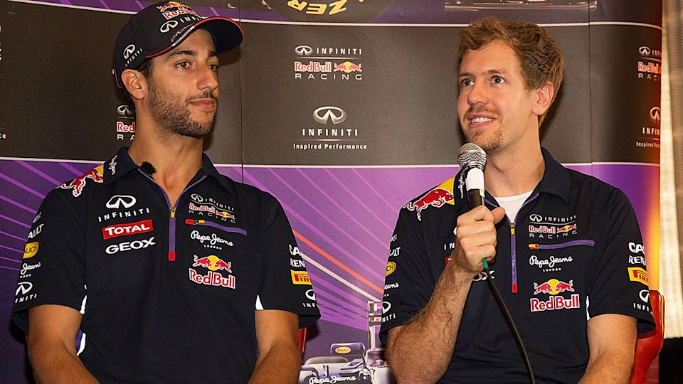 Sebastian Vettel is pictured with Daniel Ricciardo during a 2014 media appearance when the pair were F1 teammates at Red Bull Racing.