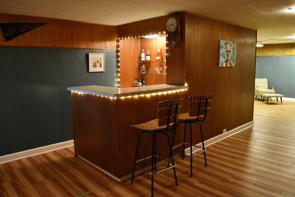 """<p>If a white space isn't your thing, you can always embrace your brown wood paneling and lean into a retro aesthetic. This blogger uses string lights, vintage prints, and a shuffleboard table to achieve a self-described """"1970s went to summer camp"""" look. </p><p><strong>See more at <a href=""""https://bridgetsbeehive.com/rumpus-room-basement-reveal/"""" rel=""""nofollow noopener"""" target=""""_blank"""" data-ylk=""""slk:Bridget's Beehive"""" class=""""link rapid-noclick-resp"""">Bridget's Beehive</a>. </strong></p><p><a class=""""link rapid-noclick-resp"""" href=""""https://go.redirectingat.com?id=74968X1596630&url=https%3A%2F%2Fwww.walmart.com%2Fip%2FHoliday-Time-Indoor-and-Outdoor-Clear-Mini-Christmas-Lights-59-300-Count-Green-Wire%2F995323450&sref=https%3A%2F%2Fwww.thepioneerwoman.com%2Fhome-lifestyle%2Fdecorating-ideas%2Fg34763691%2Fbasement-ideas%2F"""" rel=""""nofollow noopener"""" target=""""_blank"""" data-ylk=""""slk:SHOP STRING LIGHTS"""">SHOP STRING LIGHTS</a></p>"""