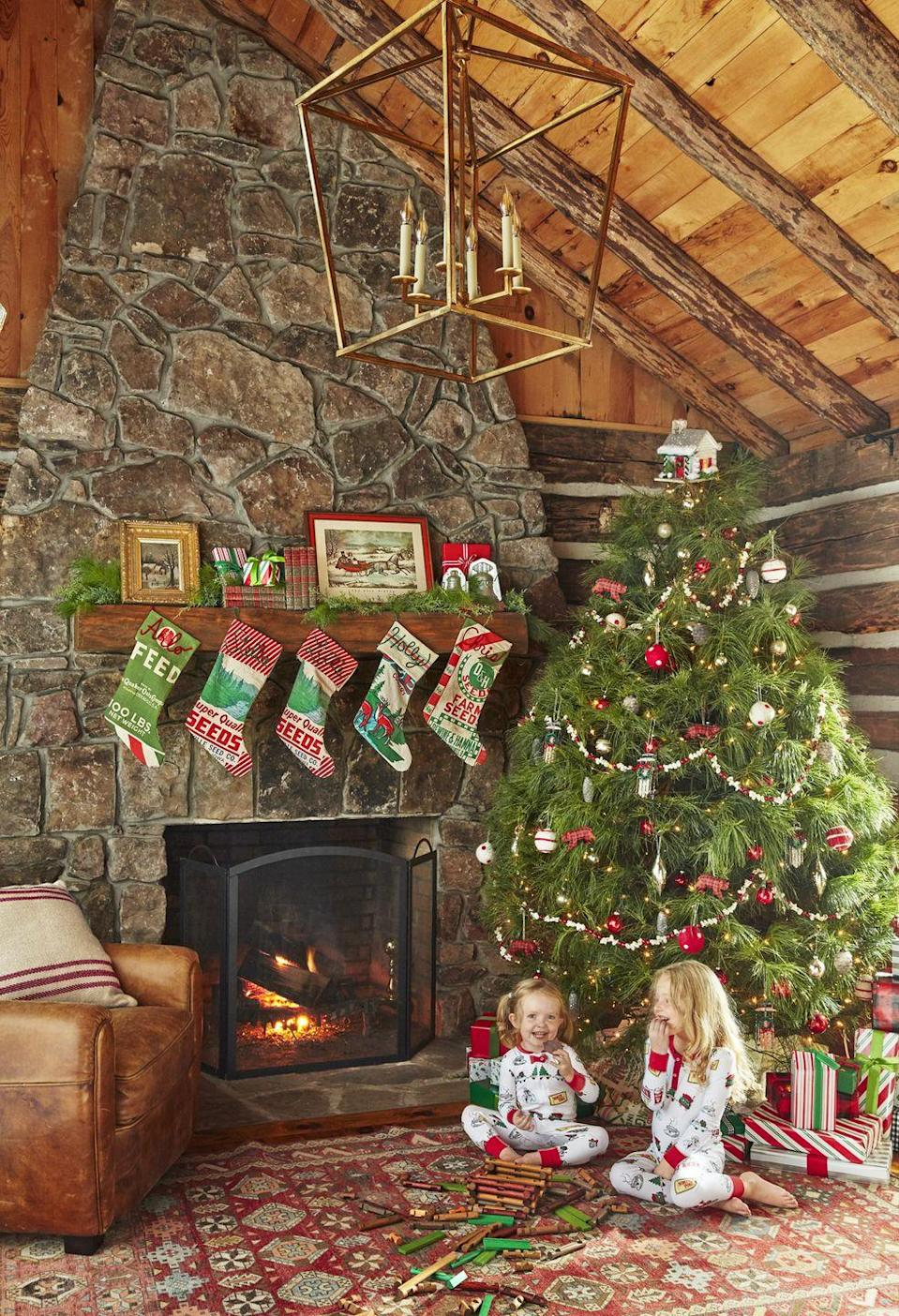 """<p>Holly's <a href=""""https://www.countryliving.com/shopping/g1407/personalized-christmas-stockings/"""" rel=""""nofollow noopener"""" target=""""_blank"""" data-ylk=""""slk:festive stockings"""" class=""""link rapid-noclick-resp"""">festive stockings</a>, made from seed sacks and monogrammed with yarn, conjure the same handcrafted spirit as the pioneer-built cabin. Similarly, the <a href=""""https://www.countryliving.com/diy-crafts/how-to/g1545/christmas-tree-toppers/"""" rel=""""nofollow noopener"""" target=""""_blank"""" data-ylk=""""slk:tree topper"""" class=""""link rapid-noclick-resp"""">tree topper</a>—a hand-constructed cabin—champions a DIY spirit. </p><p><a class=""""link rapid-noclick-resp"""" href=""""https://www.amazon.com/Aitey-Christmas-Character-Decorations-Accessory/dp/B075XK8XD8?tag=syn-yahoo-20&ascsubtag=%5Bartid%7C10050.g.1247%5Bsrc%7Cyahoo-us"""" rel=""""nofollow noopener"""" target=""""_blank"""" data-ylk=""""slk:SHOP STOCKINGS"""">SHOP STOCKINGS</a></p>"""