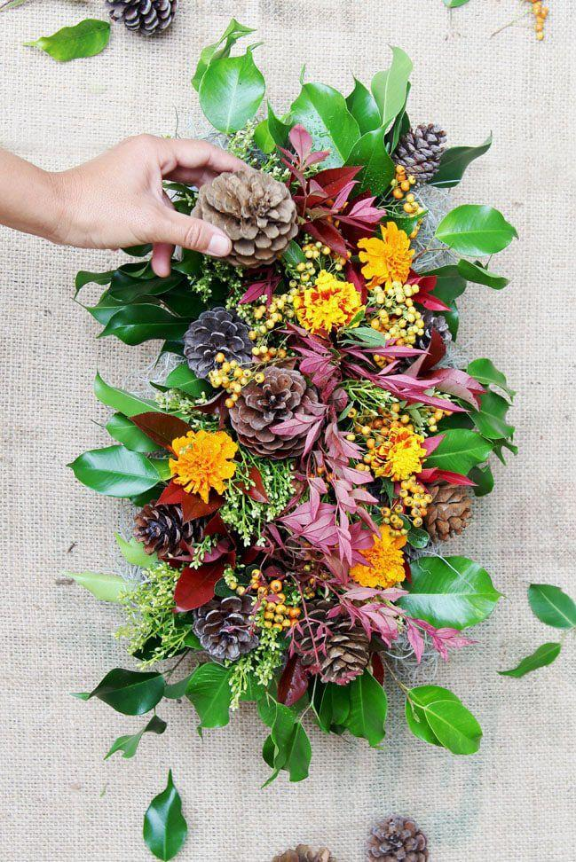 """<p>Bring some of nature's beauty indoors with this loose and casual display of autumnal blooms, leaves, and other fresh finds.</p><p><strong>Get the tutorial at </strong><a href=""""https://www.apieceofrainbow.com/diy-fall-thanksgiving-centerpiece/"""" rel=""""nofollow noopener"""" target=""""_blank"""" data-ylk=""""slk:A Piece of Rainbow"""" class=""""link rapid-noclick-resp""""><strong>A Piece of Rainbow</strong></a><strong>.</strong></p><p><a class=""""link rapid-noclick-resp"""" href=""""https://www.amazon.com/SuperMoss-24511-Black-Spruce-8-Ounce/dp/B00K80EWGA/?tag=syn-yahoo-20&ascsubtag=%5Bartid%7C10050.g.2130%5Bsrc%7Cyahoo-us"""" rel=""""nofollow noopener"""" target=""""_blank"""" data-ylk=""""slk:SHOP PINECONES""""><strong>SHOP PINECONES</strong></a></p>"""