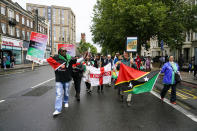 Demonstrators hold flags and placards as they take part in the annual Afrikan Emancipation Day Reparations march, in Brixton, London, Sunday, Aug. 1, 2021. Black people whose right to live in the U.K. was illegally challenged by the government marked the anniversary Sunday of the act that freed slaves throughout the British Empire, drawing a direct link between slavery and the discrimination they suffered. Dozens of campaigners gathered in Brixton, a center of the Black community in south London, to back the international drive for reparations for the descendants of enslaved Africans and demand legislation to compensate legal residents who were threatened with deportation in what is known as the Windrush Scandal. (AP Photo/Alberto Pezzali)