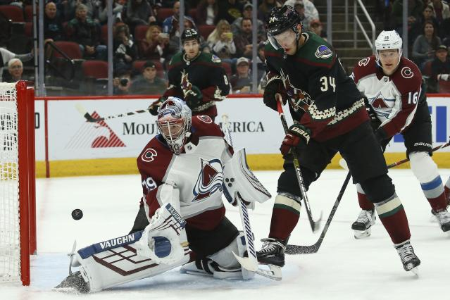 Colorado Avalanche goaltender Pavel Francouz, left, makes a save on a shot by Arizona Coyotes center Carl Soderberg (34) during the second period of an NHL hockey game Saturday, Nov. 2, 2019, in Glendale, Ariz. (AP Photo/Ross D. Franklin)