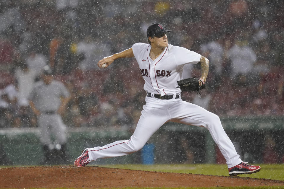 Boston Red Sox starting pitcher Tanner Houck delivers to the New York Yankees during a rain shower in the fifth inning of a baseball game at Fenway Park, Thursday, July 22, 2021, in Boston. (AP Photo/Elise Amendola)