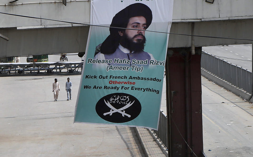 A banner of demands with a portrait of Saad Rizvi, the leader of Tehreek-e-Labiak Pakistan, a radical Islamist political party, hangs on a bridge while his supporters block a road during a sit-in protest against the arrest of Rizvi, in Lahore, Pakistan, Wednesday, April 14, 2021. Pakistani security forces swinging batons and firing teargas moved before dawn Wednesday to clear sit-ins by protesting Islamists in the garrison city of Rawalpindi and elsewhere after five people died in earlier clashes, officials said. (AP Photo/K.M. Chaudary)