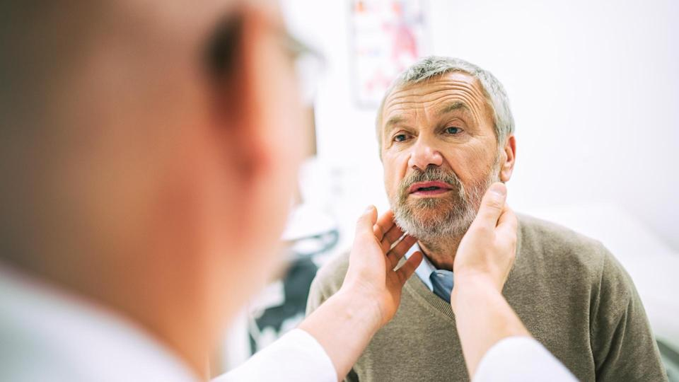 Over the shoulder view of a doctor touching a patient's throat while doing a medical exam.