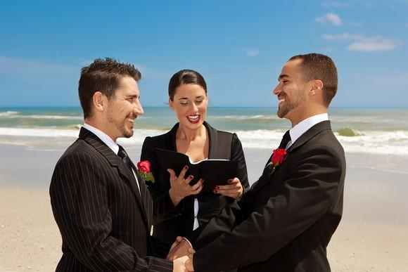 Two men in formal wear holding hands facing each other in front of an officiant holding a book, on a beach.