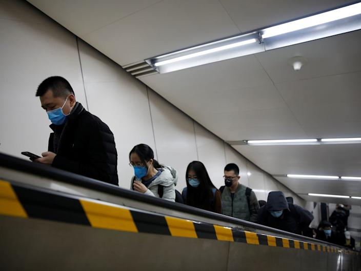 People exit a subway station in Beijing, China, on March 30, 2020.
