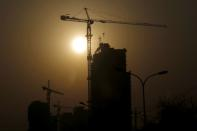 FILE PHOTO: A crane at a construction site is silhouetted against the rising sun in Beijing