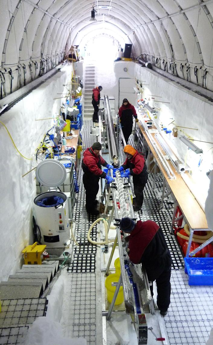 In this Nov. 22, 2012 photo released by scientist Nancy Bertler, scientists and staff work on ice cores they've collected, on Roosevelt Island, Antarctica. The team dug a trench in the snow to work from. Antarctica's pristine habitat provides a laboratory for scientists studying the effects of climate change. (AP Photo/Courtesy Nancy Bertler)