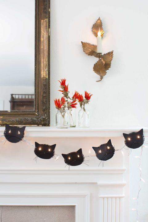 """<p>Help your kids cut out purr-fect black cat faces for a glowing garland.</p><p><strong>To make:</strong> <strong>Step 1:</strong> Download our <a href=""""http://clv.h-cdn.co/assets/cm/15/24/5578a73fa1435_-_Cat_silo.pdf"""" rel=""""nofollow noopener"""" target=""""_blank"""" data-ylk=""""slk:cat face template"""" class=""""link rapid-noclick-resp"""">cat face template</a><em>.</em><br><br><strong><strong>Step 2:</strong> </strong>Using a white pencil, trace the template onto black card stock and cut out desired number of faces.</p><p><strong><strong>Step</strong> 3: </strong>Fringe the sides of the cat's face and the top of its head with scissors. </p><p><strong><strong>Step 4:</strong> </strong>For each cat, cut three pieces of black waxed twine, about 4"""" long. Knot them together in the center of the twine, and glue to the cat's face as whiskers.</p><p><strong><strong><strong>Step 5:</strong></strong> </strong>Toward the horizontal center of the cat's face, use a standard single-hole punch to create holes for eyes about 21/2"""" apart.</p><p><strong><strong><strong>Step 6:</strong></strong> </strong>Hang string lights and position cat faces on 2 lightbulbs, one in each eye hole. </p>"""