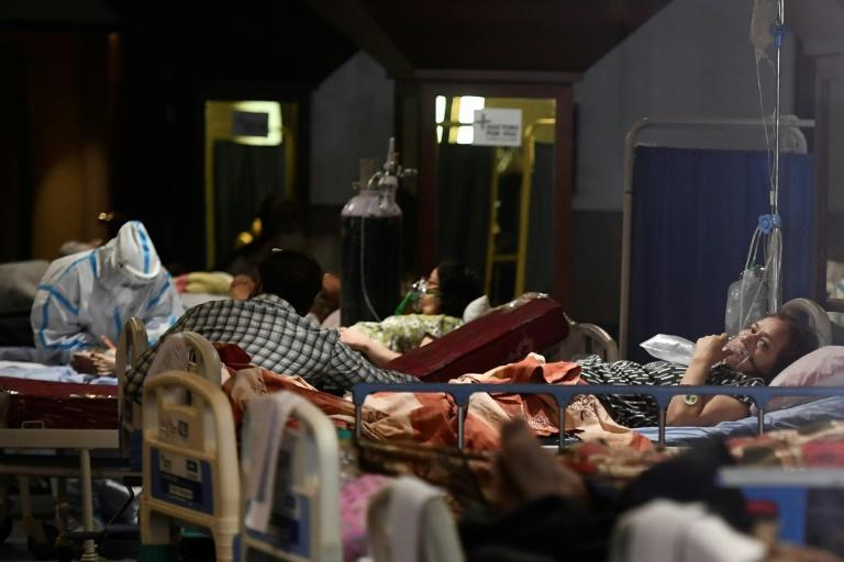 Patients rest inside a banquet hall used as a makeshift coronavirus ward in New Delhi