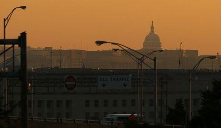 The dome of the U.S. Capitol rises over the Pentagon and other federal buildings in Washington during sunrise, October 2, 2013. REUTERS/Kevin Lamarque