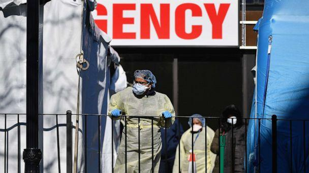 PHOTO: Medical workers outside Elmhurst Hospital Center, in the Queens borough of New York City, on March 26, 2020. The hospital reported 13 COVID-19 patients died in a 24-hour span. (Angela Weiss/AFP via Getty Images)