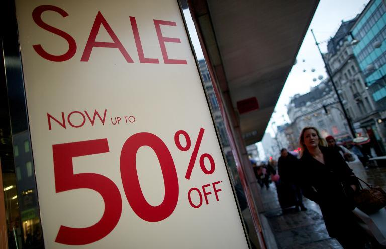 Shoppers walk past sale signs on Oxford Street in central London on January 4, 2014