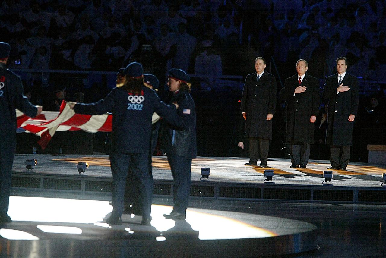 400804 08: (NEWSWEEK, US NEWS, MACLEANS AND GERMANY OUT) (L-R) Dr. Jacques Rogge, President of the IOC, U.S. President George W. Bush and SLOC President Mitt Romney watch as U.S. athletes hold the flag from Ground Zero during the National Anthem at the Opening Ceremony of the Salt Lake City Winter Olympic Games at the Rice-Eccles Olympic Stadium February 8, 2002 in Salt Lake City, UT. (Photo by Al Bello/Getty Images)