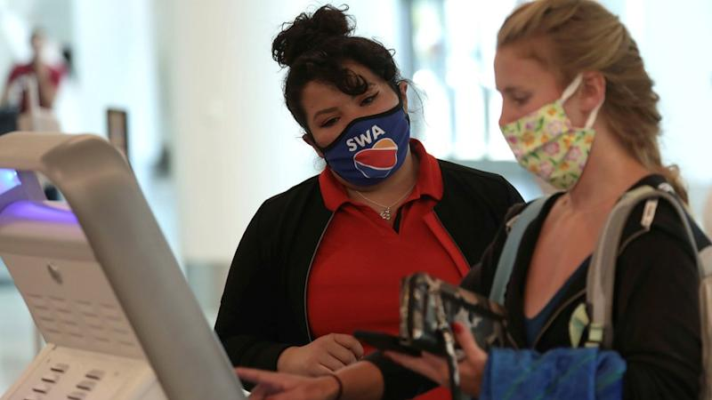 A Southwest Airlines Co. employee wears a protective mask while assisting a passenger at Los Angeles International Airport (LAX) on an unusually empty Memorial Day weekend during the outbreak of the coronavirus disease (COVID-19) in Los Angeles