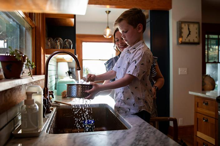Megan Warren and her son, Reeve, 6, prepare dinner together at their home in Portland, Ore., on July 26. Warren says that when the family lived in Los Angeles, they tried to save water from cooking to use for watering their plants because they had to conserve water as much as possible.
