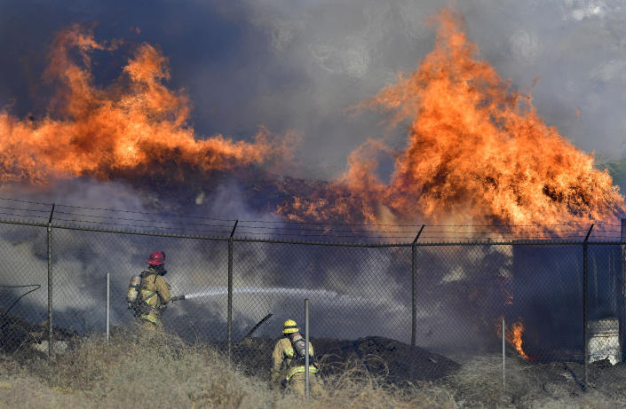 Firefighters battle a mulch and pallet fire burning out of control, fanned by Santa Ana winds in and around a recycling yard near Wilson Street and Fleetwood Drive in Riverside, Calif., Thursday, Dec. 3, 2020. Firefighters from both Riverside and San Bernardino County, along with assistance from Colton, Rialto and Riverside City Fire fought the blaze. (Will Lester/The Orange County Register via AP)