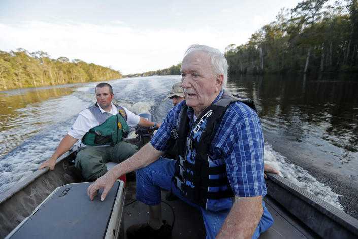 William Larymore, left, of the South Carolina Department of Natural Resources, and Salvatore Cirencione, of the State Law Enforcement Division, partially visible behind, help resident Franklin Bessemer, who lives on the river, back to a pier on the Waccamaw River in Conway, S.C., Monday, Sept. 17, 2018. Bessemer's boat had quit while he was checking on his home as residents evacuate. The river is expected to flood in the coming days due heavy rains from Hurricane Florence. (AP Photo/Gerald Herbert)