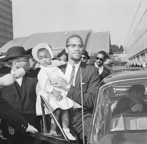 PHOTO: In this May 21, 1964, file photo, Malcolm X carries his daughter, Ilyasah, as he enters car at John F. Kennedy International Airport in New York. (Bettmann Archive via Getty Images, FILE)