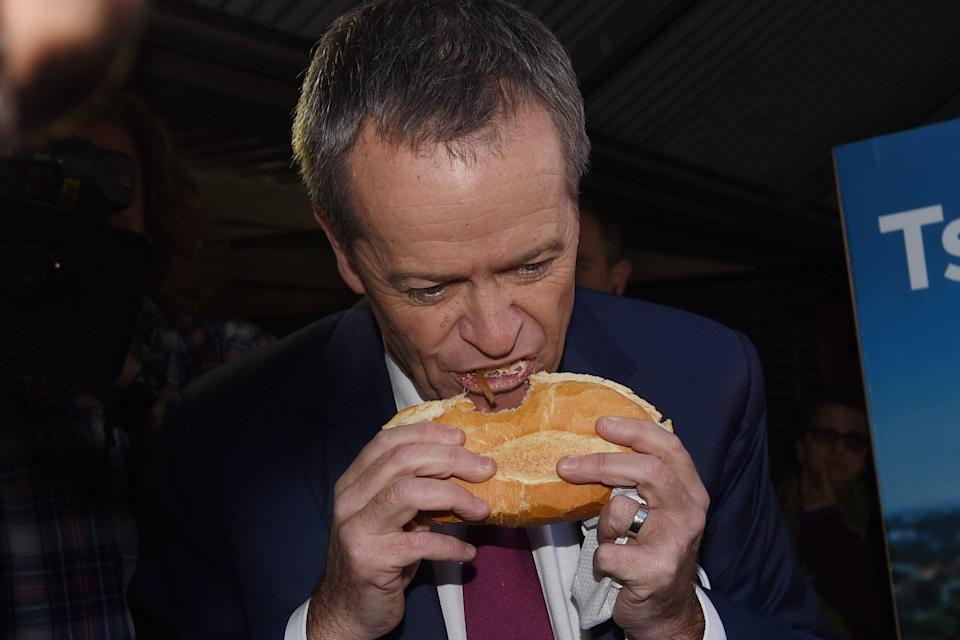 Leader of the Opposition Bill Shorten eats a sausage sandwich at Strathfield North Public School polling booth as part of the 2016 Election Day in Sydney, Saturday, July 2, 2016. (AAP Image/Mick Tsikas)