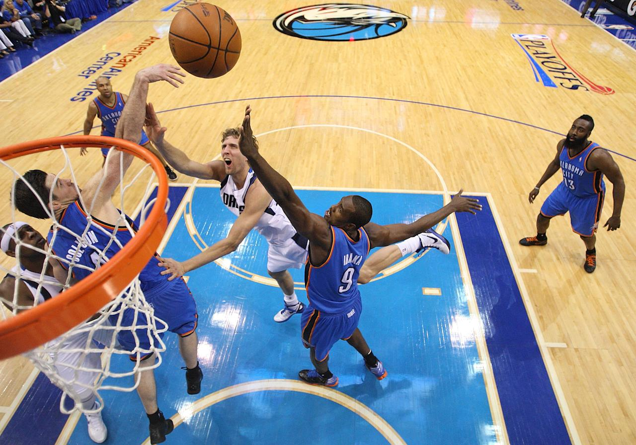 DALLAS, TX - MAY 05:  Dirk Nowitzki #41 of the Dallas Mavericks takes a shot against Serge Ibaka #9 and Nick Collison #4 of the Oklahoma City Thunder during Game Four of the Western Conference Quarterfinals in the 2012 NBA Playoffs at American Airlines Center on May 5, 2012 in Dallas, Texas. NOTE TO USER: User expressly acknowledges and agrees that, by downloading and or using this photograph, User is consenting to the terms and conditions of the Getty Images License Agreement.  (Photo by Ronald Martinez/Getty Images)