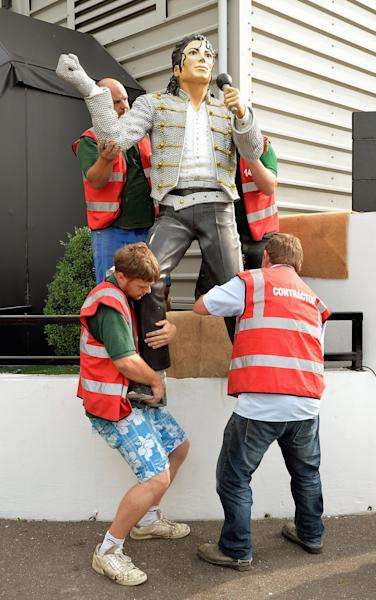 A group of stonemasons remove the statue of US performer Michael Jackson, that was erected by previous owner Mohammed al Fayed, on the north west corner of Fulham Football Club, in London, Wednesday Sept. 25, 2013. The controversial Michael Jackson statue which has stood outside Fulham's Craven Cottage ground for over two years was removed on Wednesday. Al Fayed sold the west London club to Shahid Khan in July and, after consulting with supporters, the American businessman decided to pull the 7ft 6in statue down. (AP Photo/PA, John Stillwell) UNITED KINGDOM OUT