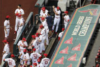 FILE - In this July 24, 2020, file photo, members of the St. Louis Cardinals wait to be introduced before the start of a baseball game against the Pittsburgh Pirates in St. Louis. The Cardinals 4-game series at Detroit was postponed Monday, Aug. 3, 2020, after more Cardinals players and staff staffers test positive for COVD-19. The series was to have been played in Detroit from Tuesday through Thursday. (AP Photo/Jeff Roberson, File)