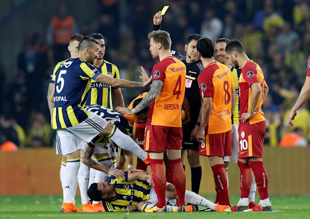 Soccer Football - Turkish Super League - Fenerbahce S.K vs Galatasaray - Sukru Saracoglu Stadium, Istanbul, Turkey - March 17, 2018 Galatasaray's Fernando is shown a yellow card by referee Bulent Yildirim REUTERS/Murad Sezer