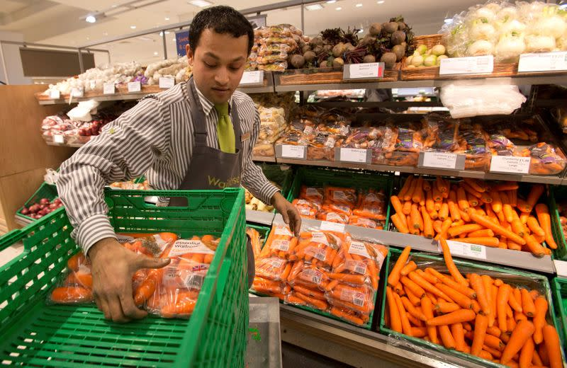 FILE PHOTO: A worker stocks produce shelves in the Canary Wharf store of Waitrose in London