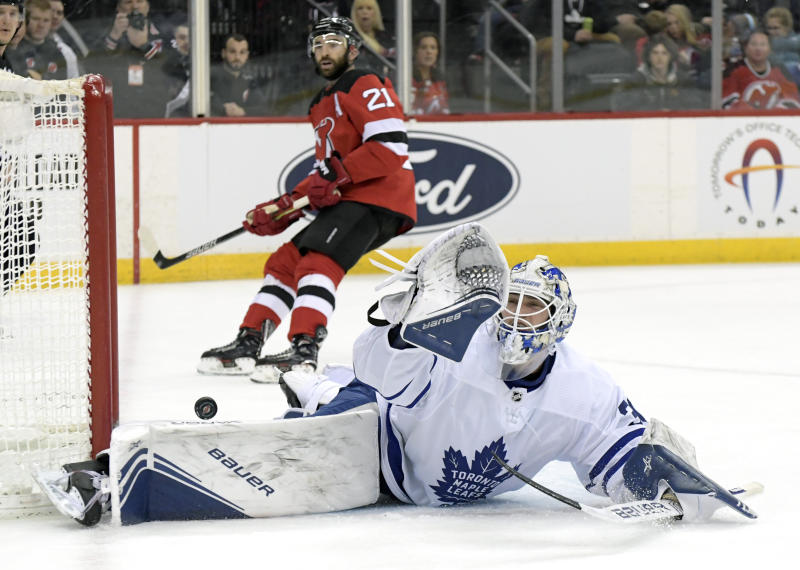 Toronto Maple Leafs goaltender Michael Hutchinson (30) cannot stop the puck as it goes into the net for a goal by New Jersey Devils left wing Jesper Bratt (not shown) as Devils right wing Kyle Palmieri (21) looks on during the second period of an NHL hockey game Friday, Dec. 27, 2019, in Newark, N.J. (AP Photo/Bill Kostroun)