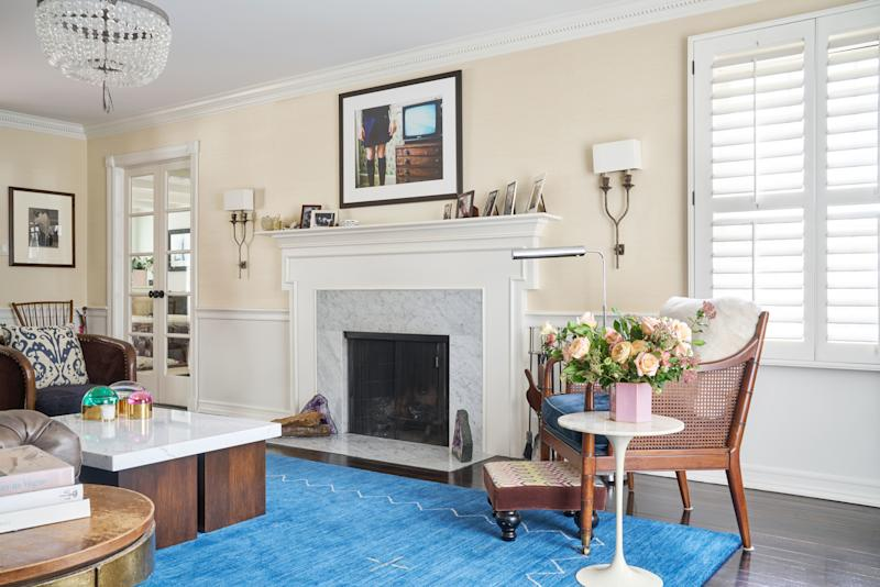 "Wark added a vanilla—""not yellow,"" he says—grasscloth wall covering above the wainscoting to make the living room more cheery. Another bright idea? Replacing the original dark fireplace with white Carrara marble."