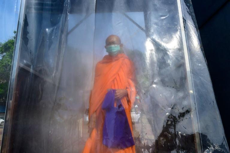 A Buddhist monk is sprayed with disinfectant in a special cabin during a mass testing event