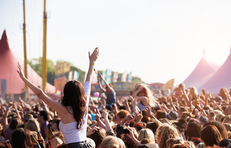 Crowd of people enjoying themselves at outdoor music festival.