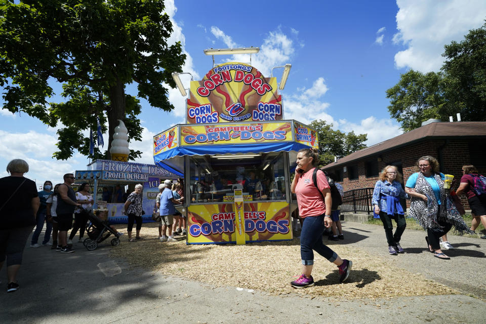 Visitors at the Iowa State Fair walk past a corn dog stand, Monday, Aug. 16, 2021, in Des Moines, Iowa. At the Iowa State Fair in Des Moines, where a million people are expected for the 11-day event, public health officials hope a vaccination station set up by pharmacists working for the Hy Vee food store chain will entice some of the vaccine-hesitant to get their shots. Visitors are packing in to state fairs in multiple Midwest states as COVID activity is increasing, raising concerns about the potential for rapidly accelerating spread of the delta variant of the COVID-19 virus. (AP Photo/Charlie Neibergall)