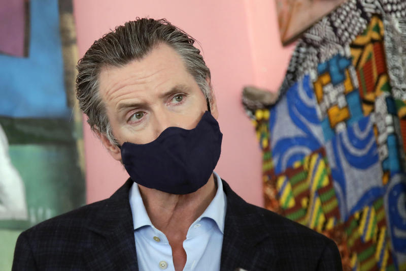FILE - In this June 9, 2020, file photo, California Gov. Gavin Newsom wears a protective mask on his face while speaking to reporters at Miss Ollie's restaurant during the coronavirus outbreak in Oakland, Calif. Gov. Newsom's administration on Thursday, June 18, 2020, mandated that Californians wear masks in most indoor settings as the state continues to battle the coronavirus.(AP Photo/Jeff Chiu, Pool, File)