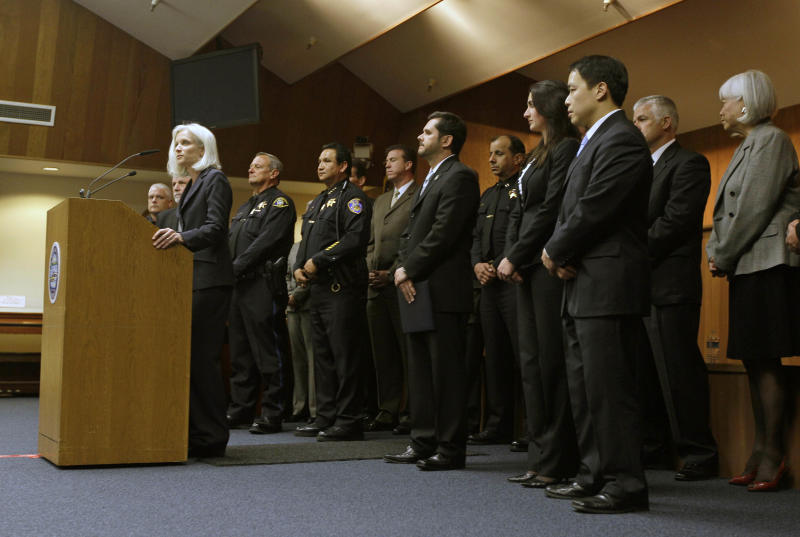 """United States Attorney Melinda Haag, with law enforcement representatives behind her, announces the arrests of 13 members and associates of the 500 Block/C Street gang during a news conference in South San Francisco, Calif., Thursday, May 3, 2012. Three Immigration and Customs Enforcement agents were shot and injured Thursday while serving """"high-risk"""" warrants in the San Francisco Bay area, authorities said. The agents suffered non-life threatening injuries during an early-morning raid in Petaluma in connection with a 2010 gang-related triple homicide. (AP Photo/Eric Risberg)"""