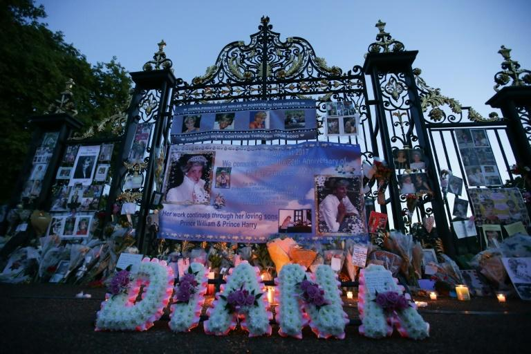 Floral tributes, candels and photographs are seen outside one of the entrances of Kensington Palace in London on August 31, 2017, to mark the 20th anniversary of the death of Diana, Princess of Wales