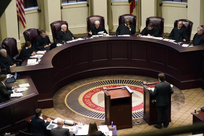 Mississippi Supreme Court Chief Justice Michael Randolph, center, questions attorney Justin Matheny of the Mississippi attorney general's office, during arguments over a lawsuit that challenges the state's initiative process and seeks to overturn a medical marijuana initiative that voters approved in November, Wednesday, April 14, 2021, in Jackson, Miss. (AP Photo/Rogelio V. Solis)
